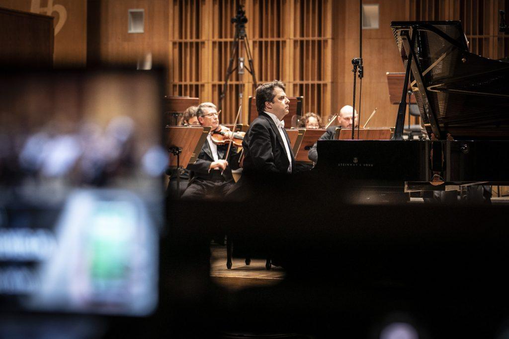 Na środku stoi fortepian, przy którym siedzi mężczyzna. Dalej kilku muzyków grających na skrzypcach.
