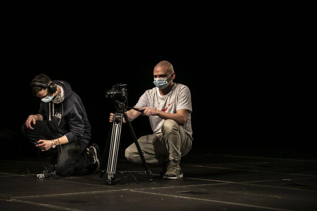 Dwóch mężczyzn w maseczkach ochronnych klęczy na jednym kolanie na scenie. Jeden z nich trzyma statyw z kamerą. Drugi, w słuchawkach patrzy w telefon.
