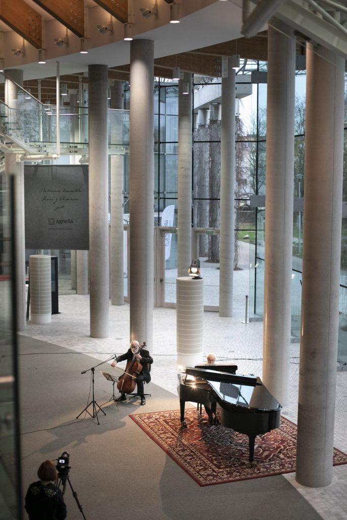 Koncert na dolnym foyer. Dwóch mężczyzn, jeden gra na fortepianie, drugi - na kontrabasie. W pewnej odległości stoi kobieta z kamerą na statywie.