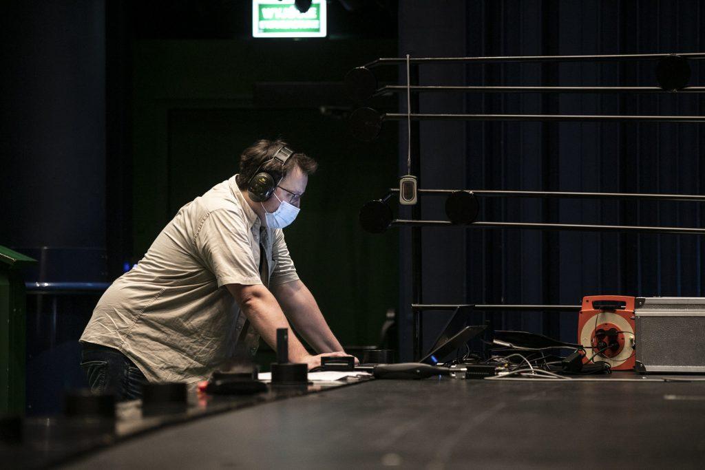 Pomiary akustyczne na dużej scenie Opery i Filharmonii Podlaskiej. Pod sceną, przed monitorami stoi mężczyzna w słuchawkach i maseczce ochronnej.