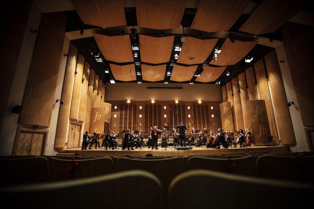 Zdjęcie zrobione z końca sali. Widownia w półmroku. Na scenie orkiestra. Na przodzie mężczyzna gra na skrzypcach, obok stoi dyrygent.