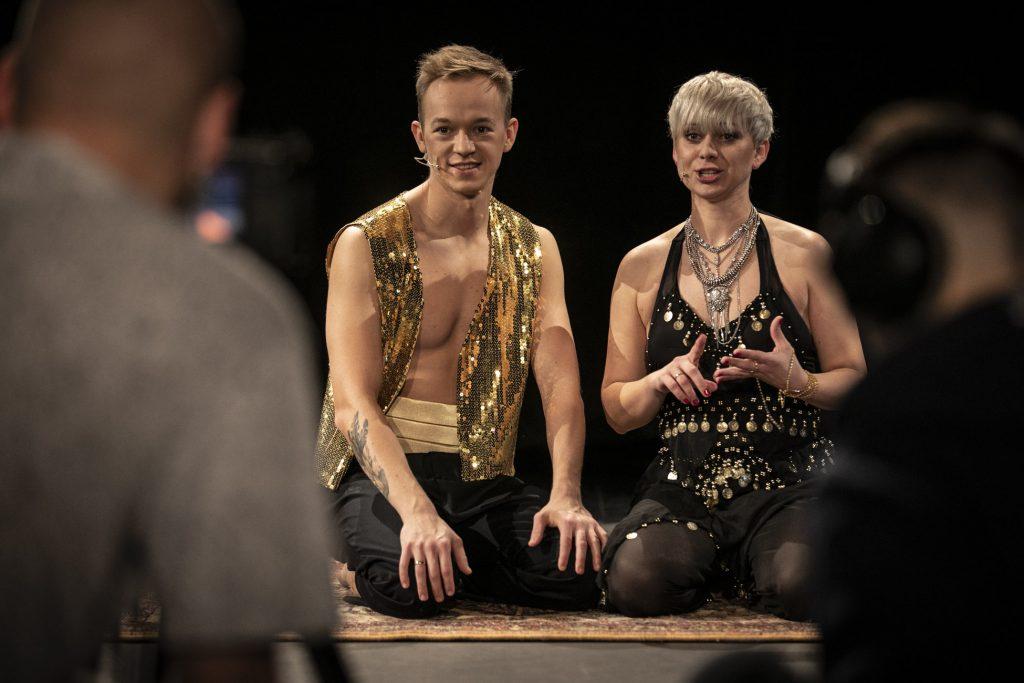 Warsztaty taneczne online. Na dywanie siedzą dwie osoby, kobieta i mężczyzna w strojach indyjskich.