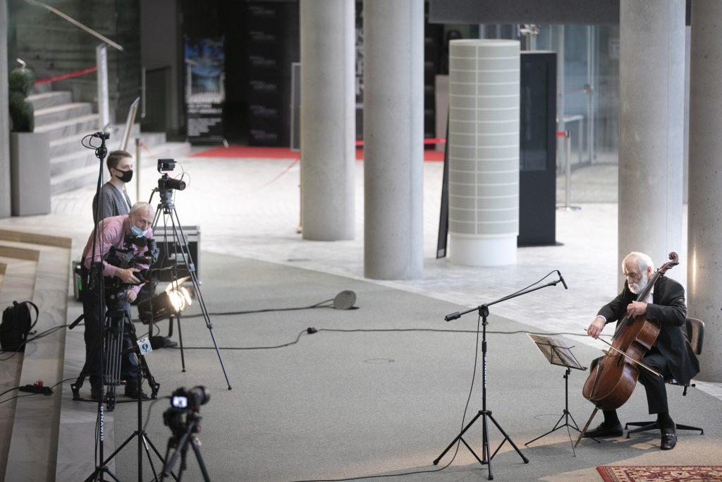 Dolne foyer. Koncert online. Po prawej stronie mężczyzna gra na kontrabasie. Po lewej kilku mężczyzn w maseczkach ochronnych stoi przy statywach z kamerami.