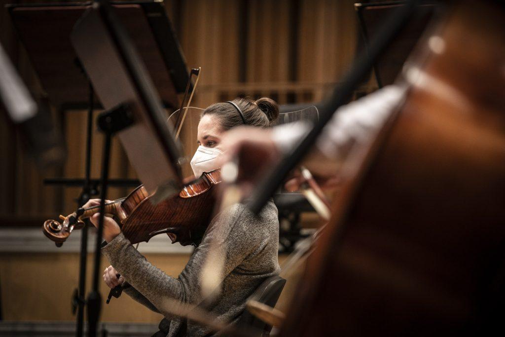 Za pulpitem widać kobietę grającą na skrzypcach. Na twarzy ma założoną maseczkę ochronną.