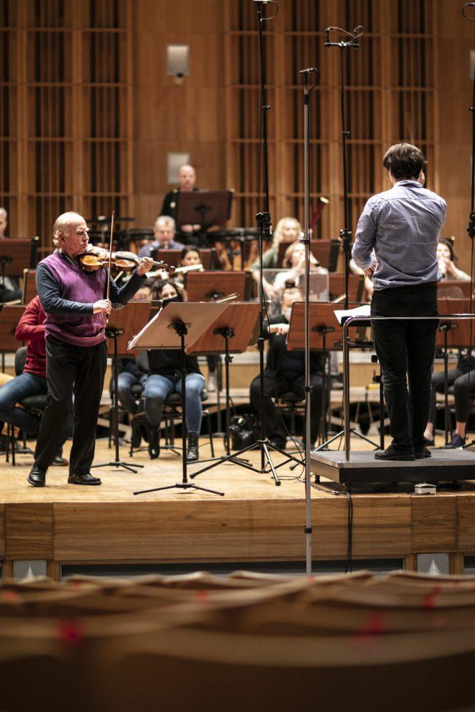 Próba do koncertu. Z przodu stoi mężczyzna grający na skrzypcach. Obok na podeście stoi dyrygent. Na scenie siedzi orkiestra.