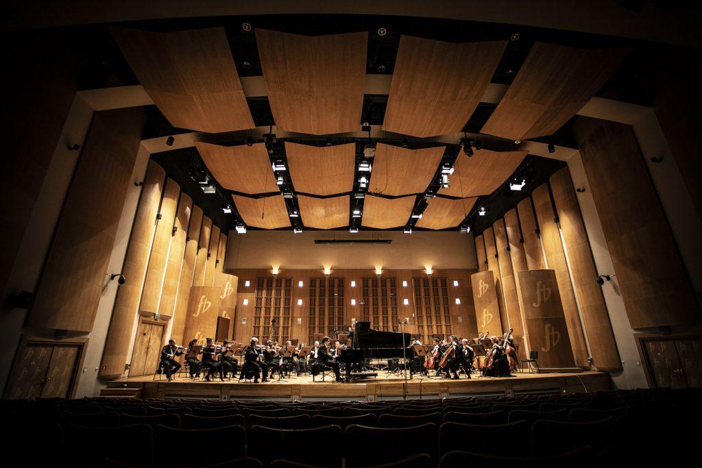 Widok z końca widowni na scenę. Widownia w półmroku. Orkiestra Opery i Filharmonii Podlaskiej podczas koncertu. Na środku sceny, przy fortepianie siedzi mężczyzna.