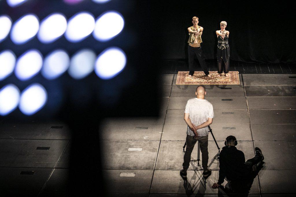 Warsztaty taneczne online. Na scenie, na dywanie stoją dwie osoby. Kobieta i mężczyzna w strojach indyjskich , z rękami wyciągniętymi do przodu. Przed nimi stoi mężczyzna przy statywie, obok na podłodze siedzi mężczyzna w słuchawkach.