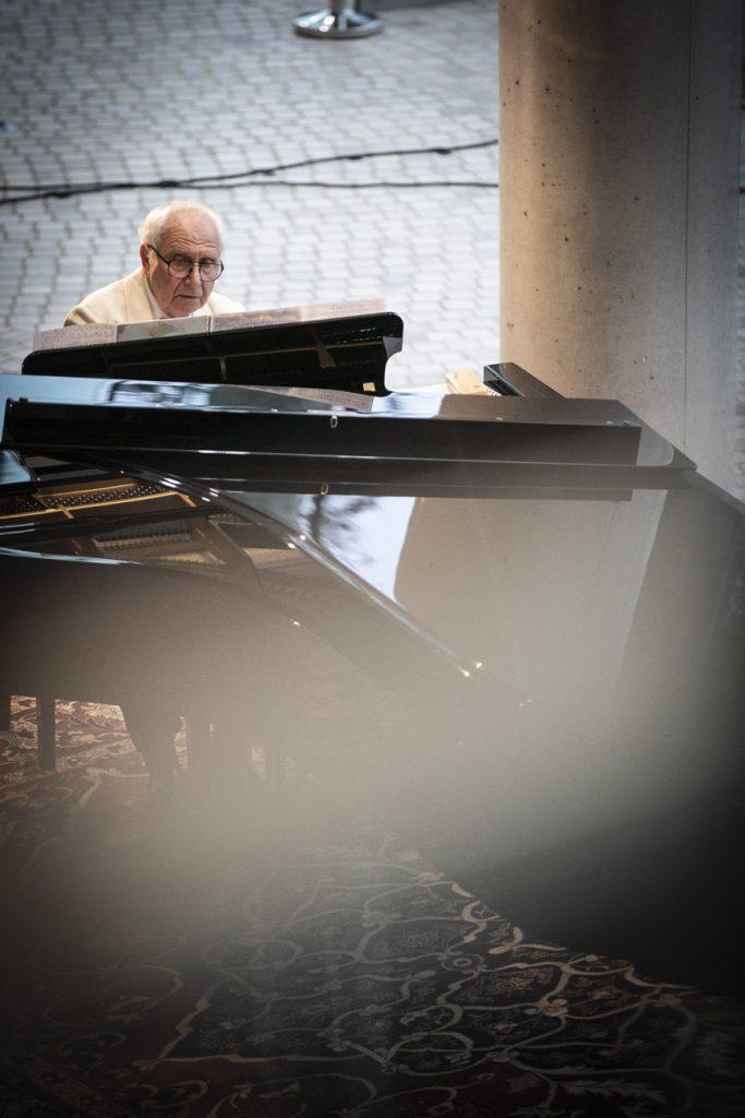 Dolne foyer. Mężczyzna gra na fortepianie.