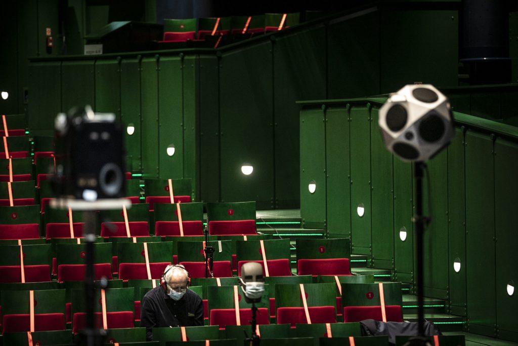 Pomiary akustyczne na dużej scenie Opery i Filharmonii Podlaskiej. Na widowni siedzi mężczyzna w słuchawkach.