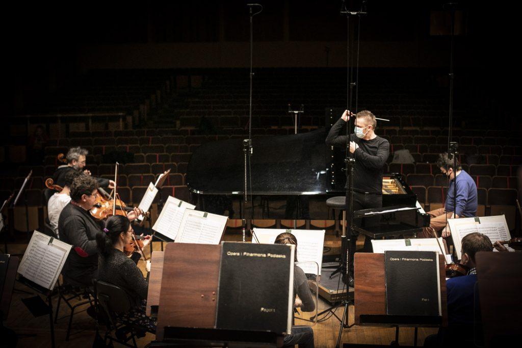 Próba do koncertu. Na scenie siedzi część kwintetu smyczkowego. Na podeście stoi dyrygent.
