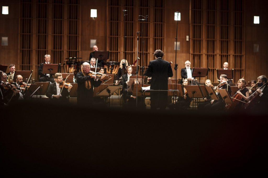Na scenie trwa koncert. Po lewej stronie stoi mężczyzna grający na skrzypcach. Po prawej stronie na podeście stoi dyrygent. Za nimi gra orkiestra Opery i Filharmonii Podlaskiej.