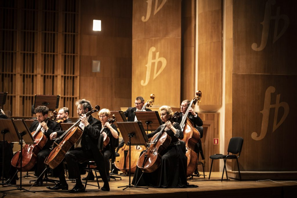 Na scenie kilku muzyków sekcji wiolonczel i kontrabasów podczas koncertu.