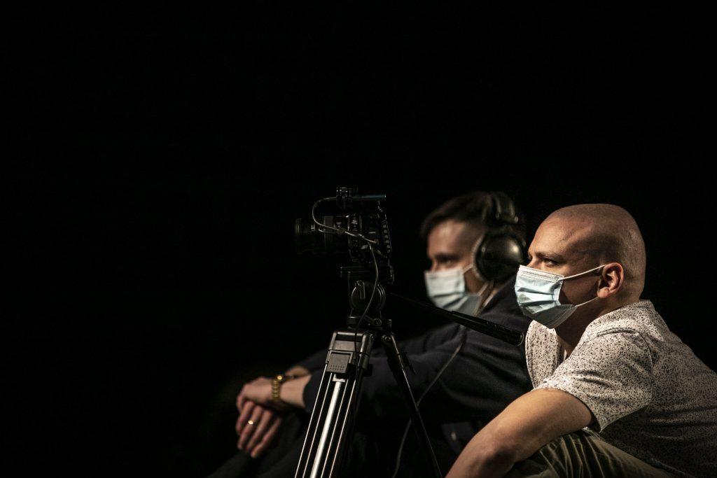 Dwóch mężczyzn w maseczkach ochronnych patrzą przed siebie. Przed jednym z nich statyw z kamerą.