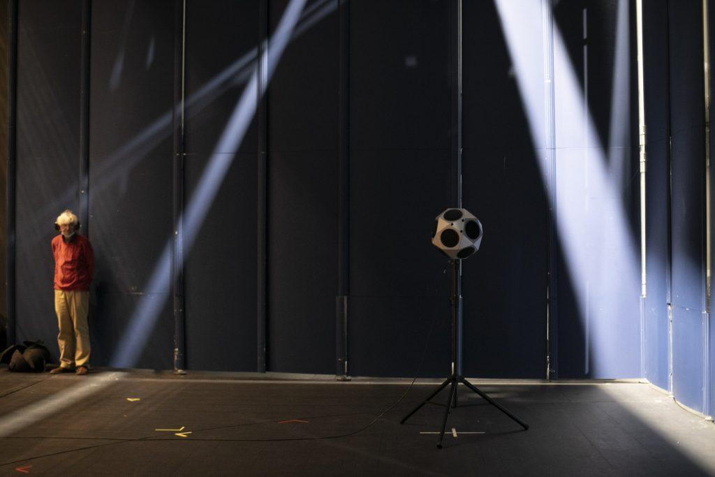 Pomiary akustyczne na dużej scenie Opery i Filharmonii Podlaskiej. Pod mobilną ścianą stoi mężczyzna w słuchawkach.