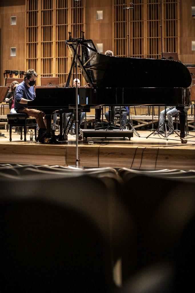 Na scenie fortepian, przy nim siedzi mężczyzna w maseczce ochronnej