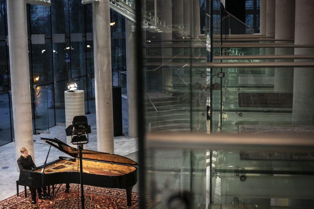 Zdjęcie zrobione z góry. Na foyer, mężczyzna gra na fortepianie.