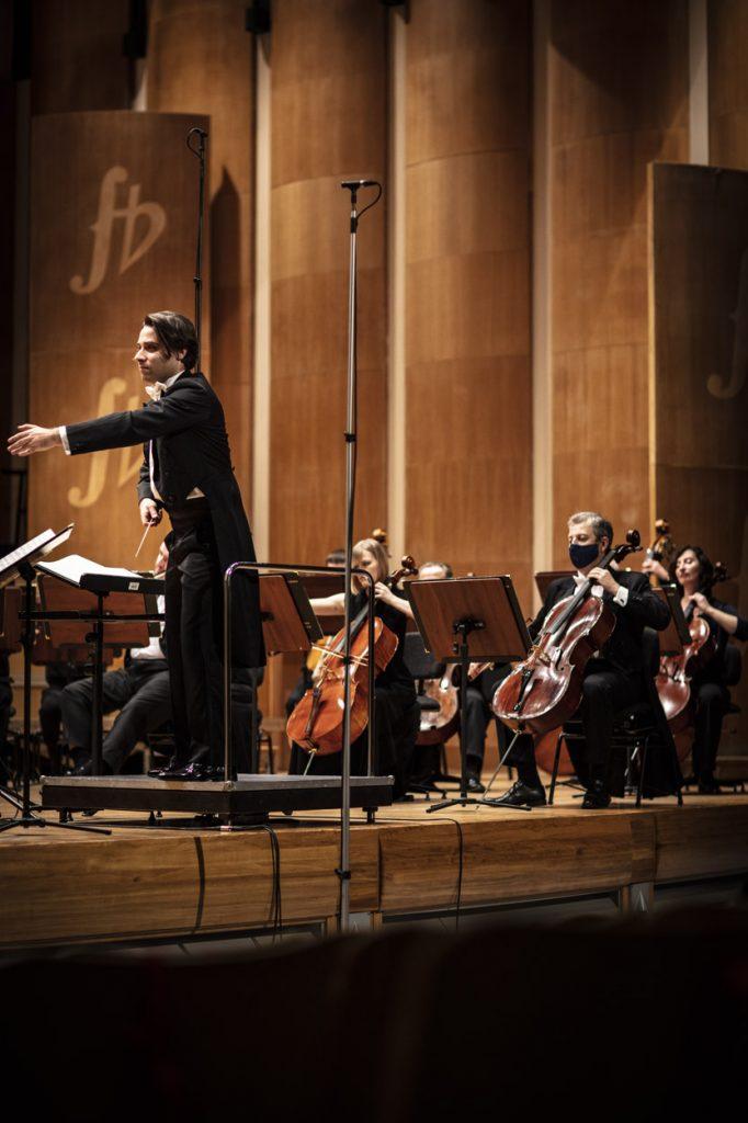 Na scenie część orkiestry i dyrygent podczas koncertu.