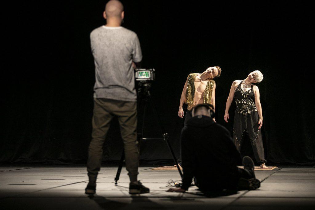 Zdjęcie z warsztatów tanecznych online. Na scenie dwie osoby, kobieta i mężczyzna w strojach indyjskich. Z przodu, tyłem stoi mężczyzna, drugi siedzi na podłodze obok.