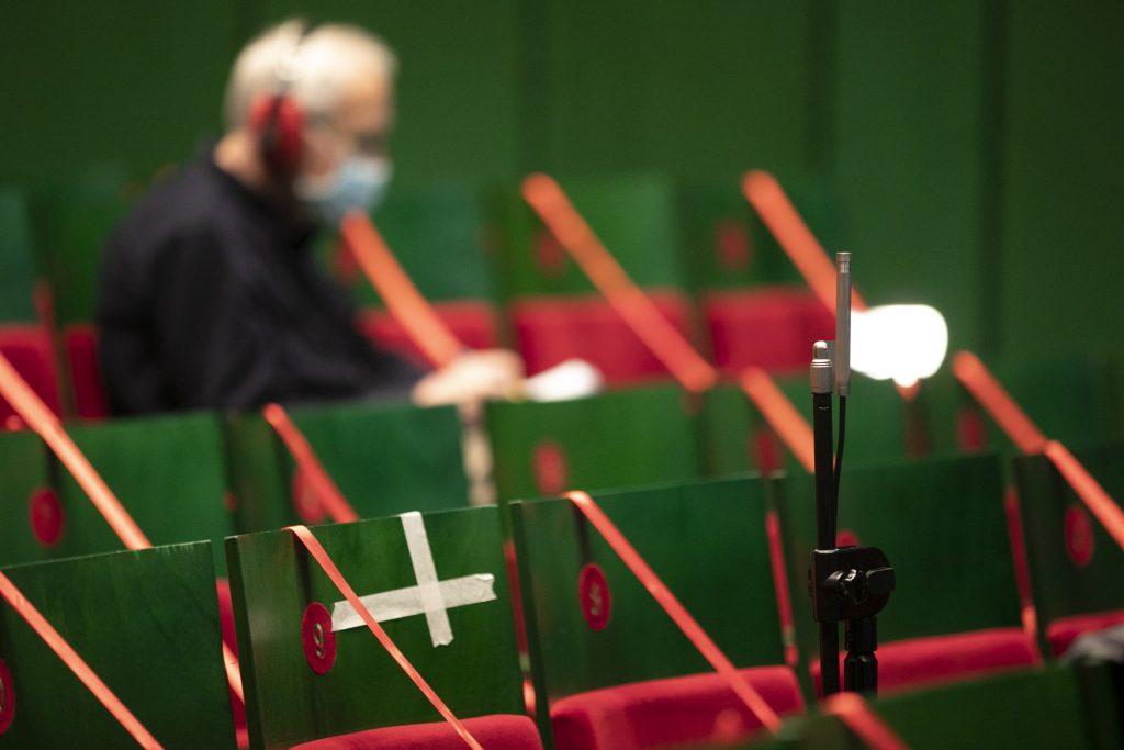 Zbliżenie na krzesła widowni. Część zabezpieczona czerwonymi wstążkami. Na jednym z krzeseł siedzi mężczyzna w słuchawkach i maseczce ochronnej.