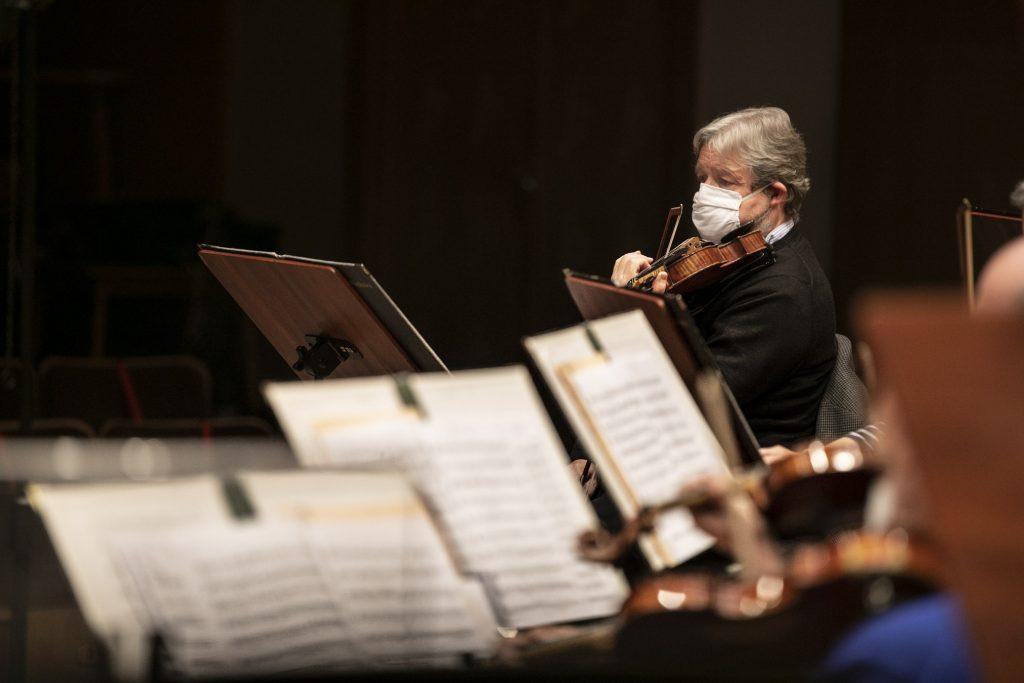 Mężczyzna w maseczce ochronnej gra na skrzypcach. Z przodu widoczne rozłożone nuty.