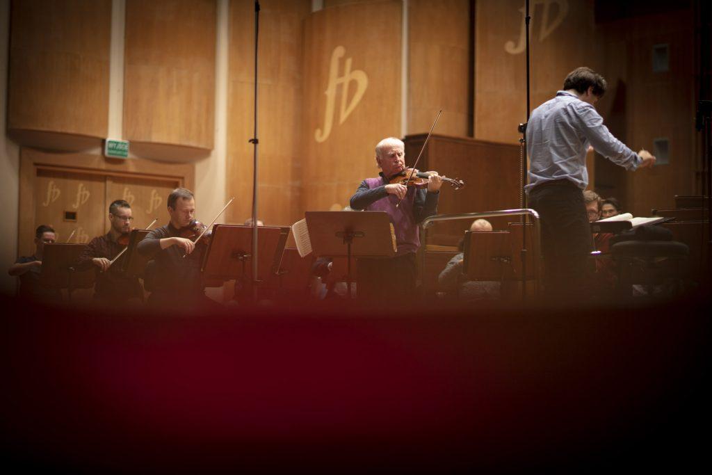 Próba do koncertu. Na środku stoi mężczyzna grający na skrzypcach. Po prawej , na podeście, z uniesionymi rękoma stoi dyrygent. Za nimi siedzi orkiestra.