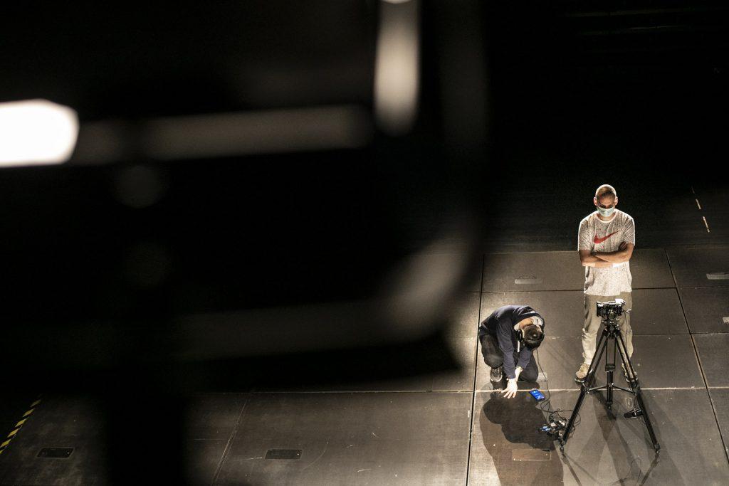 Na scenie w sali kameralnej dwóch mężczyzn. Jeden stoi przy statywie z kamerą, drugi klęczy , patrząc na telefon leżący na ziemi.