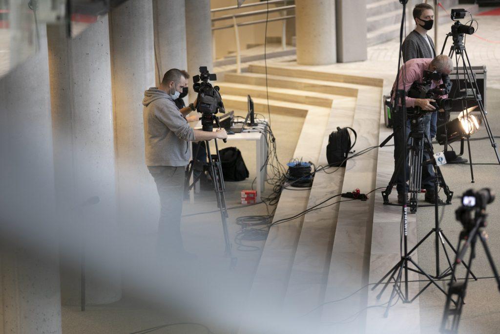 Schody na foyer dolnym. Na nich rozstawione są kamery i aparaty na statywach. Obok stoi kilku mężczyzn w maseczkach ochronnych.