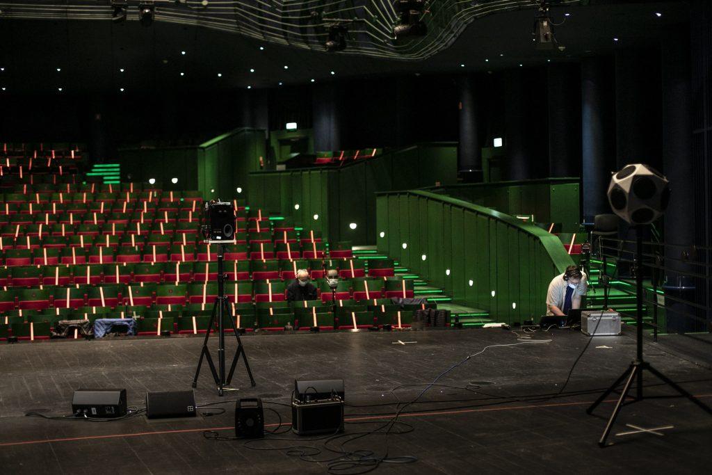 Na scenie rozstawiona jest aparatura do pomiarów akustycznych. Na widowni dwóch mężczyzn, jeden stoi przy scenie, drugi siedzi na widowni. Obydwaj mają na uszach słuchawki.