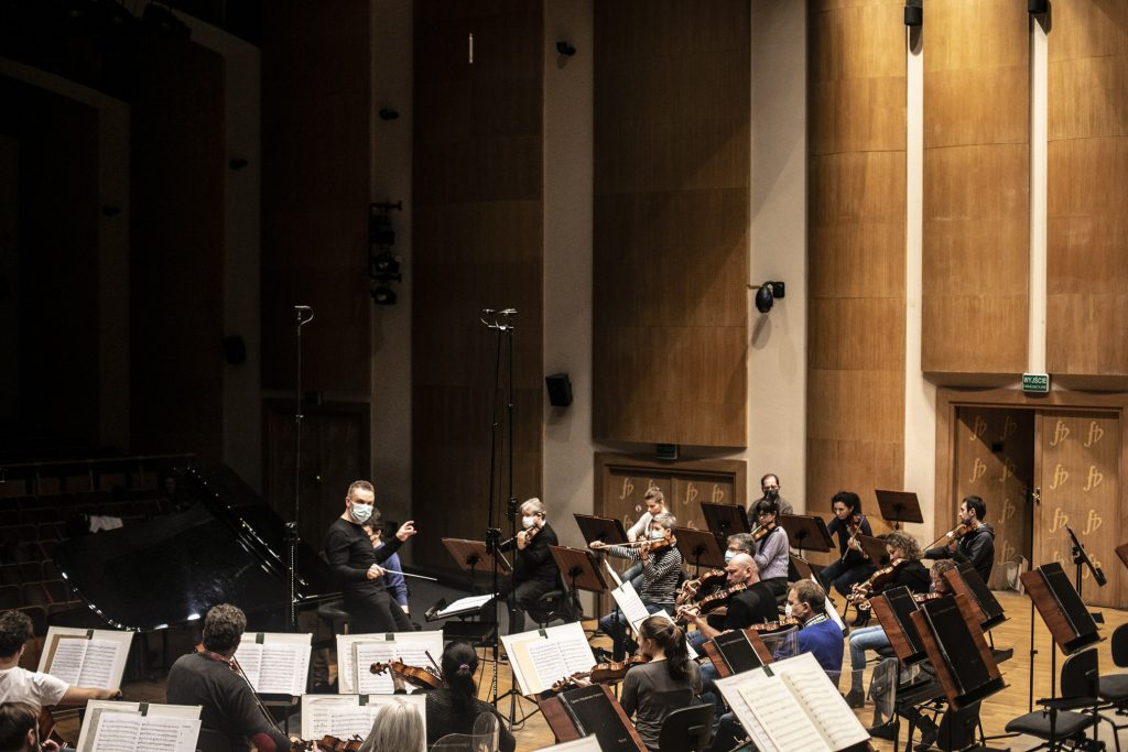 Próba do koncertu. Na scenie, przy pulpitach z rozłożonymi nutami, siedzi orkiestra wraz z dyrygentem. Większość osób na twarzach ma maseczki ochronne.