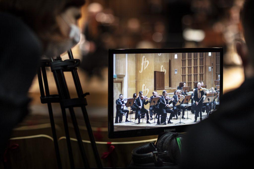 Na zdjęciu widok na monitor. Na nim widać podgląd na scenę, na której gra orkiestra.