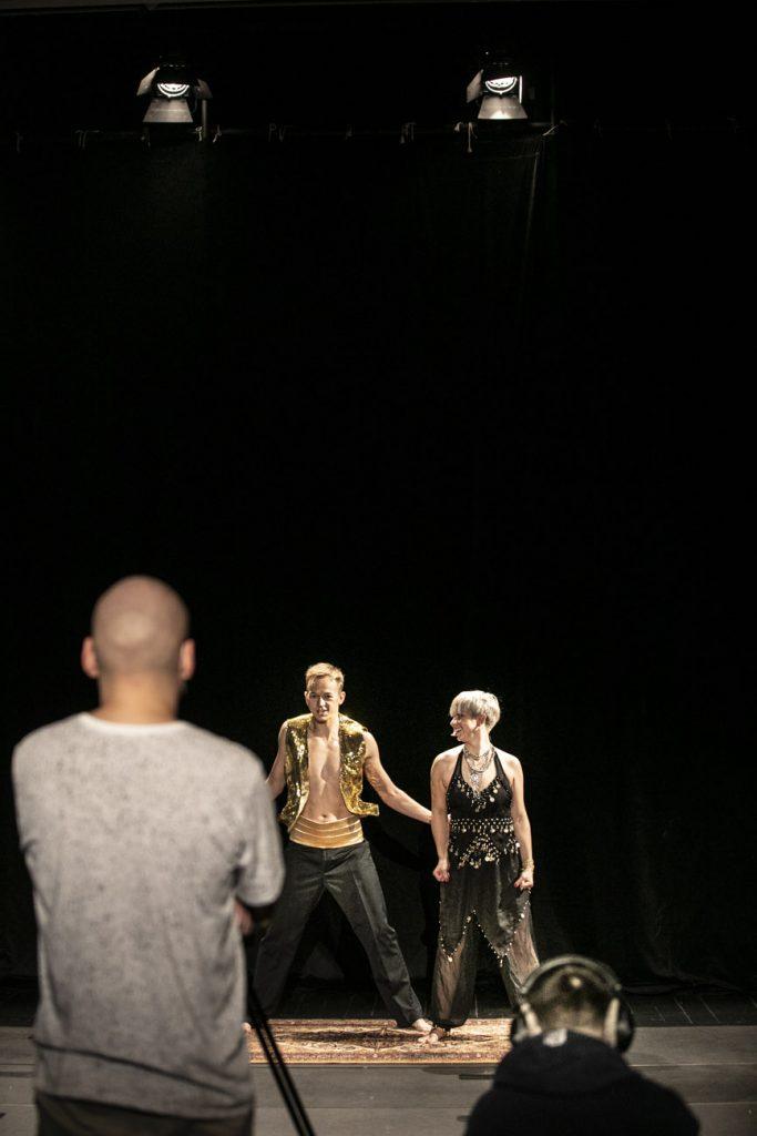 Zdjęcie z warsztatów tanecznych online. Na scenie dwie osoby, kobieta i mężczyzna w strojach indyjskich. Z przodu, tyłem stoi mężczyzna.