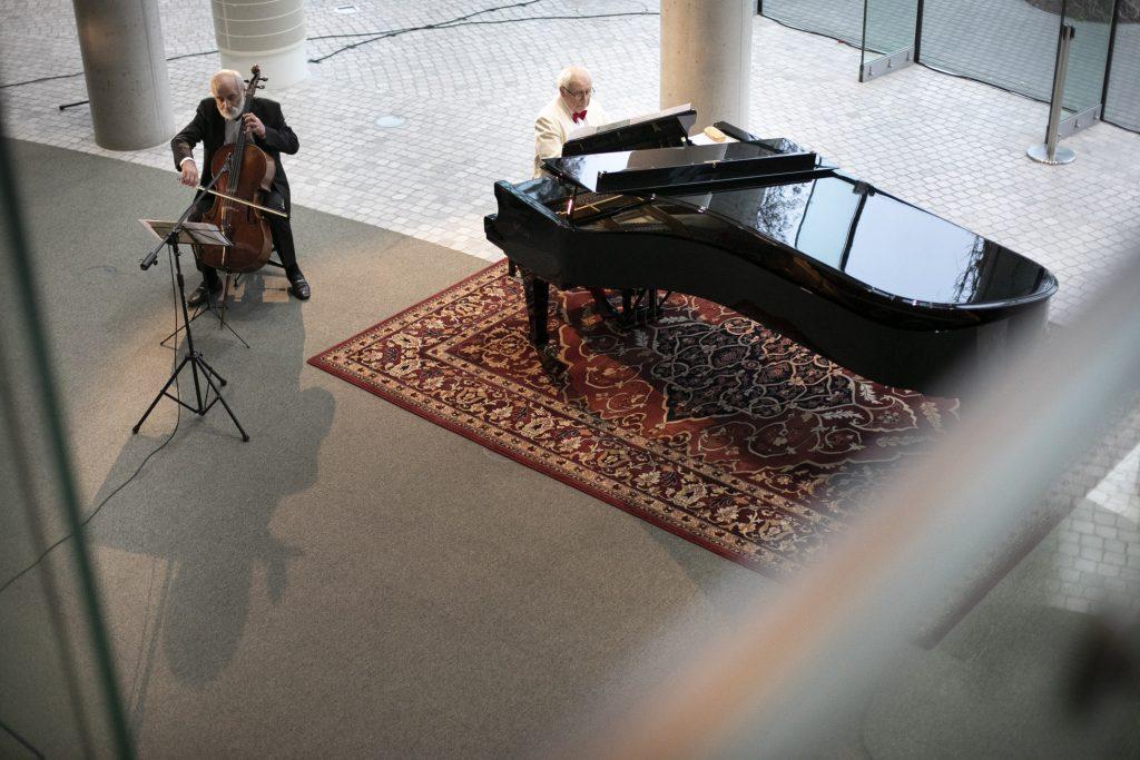 Koncert online. Na dolnym foyer siedzi dwóch mężczyzn. Jeden gra na fortepianie. Drugi z mężczyzn gra na kontrabasie.
