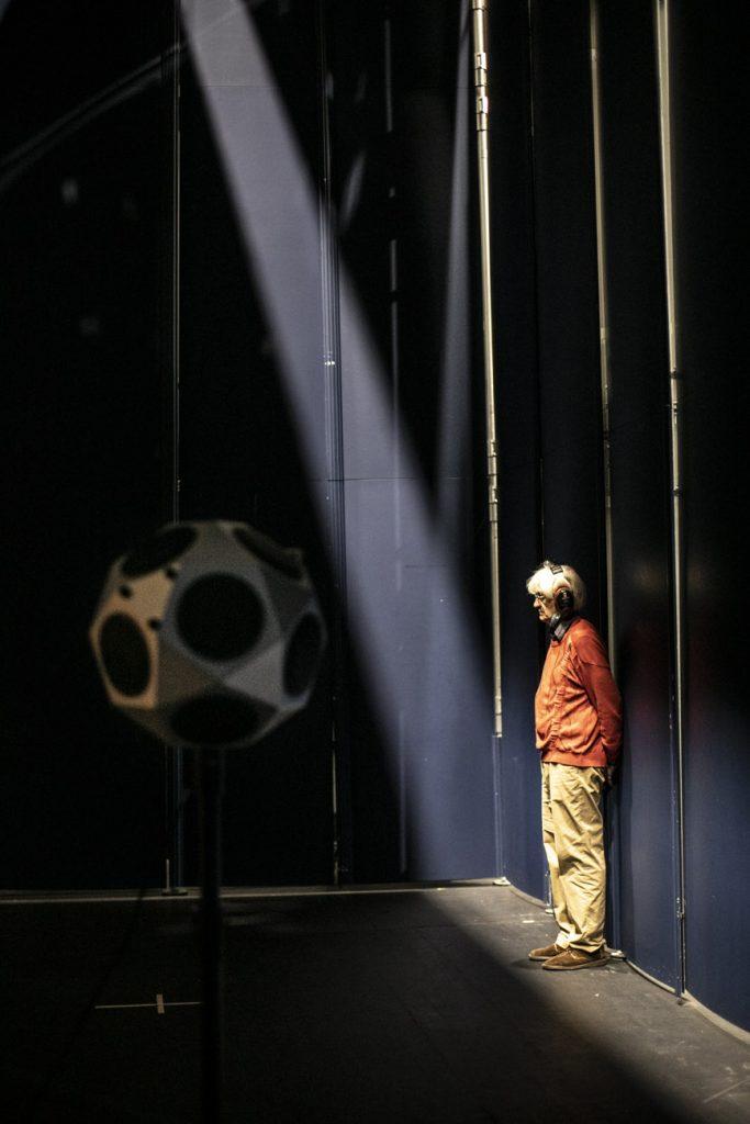 Na scenie trwają pomiary akustyczne. Pod mobilną ścianą stoi mężczyzna w słuchawkach.