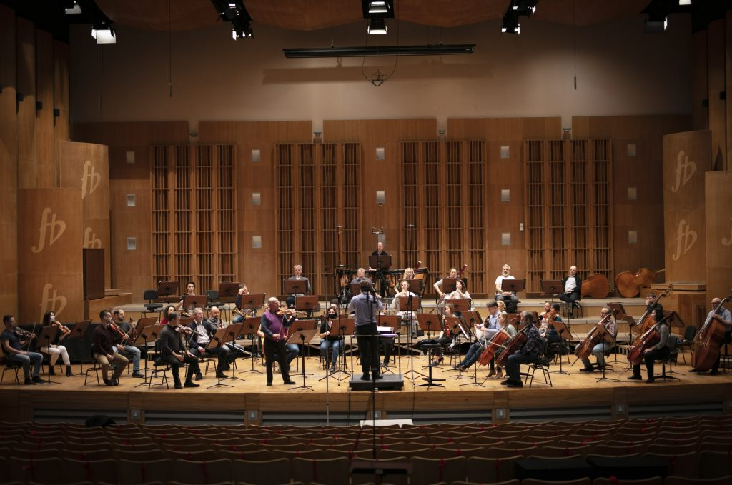 Próba do koncertu. Na scenie siedzi orkiestra. Z przodu stoi mężczyzna grający na skrzypcach. Przed nimi, na podeście stoi dyrygent.