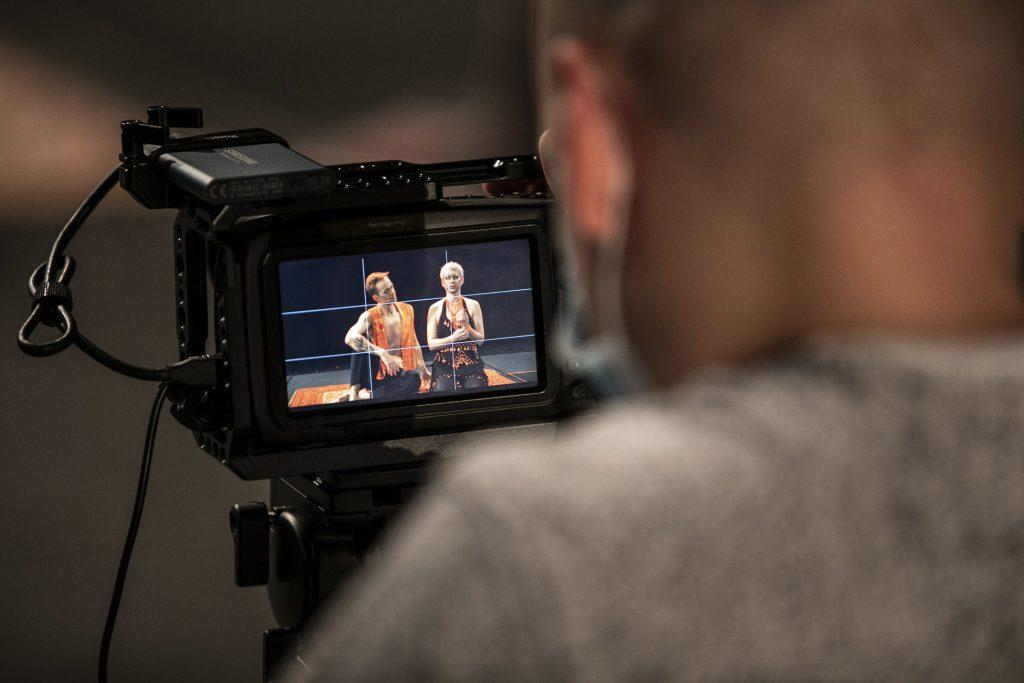 Na zdjęciu widok na kamerę, na monitorze wyświetla się para w strojach indyjskich. Kobieta i mężczyzna siedzą na dywanie.
