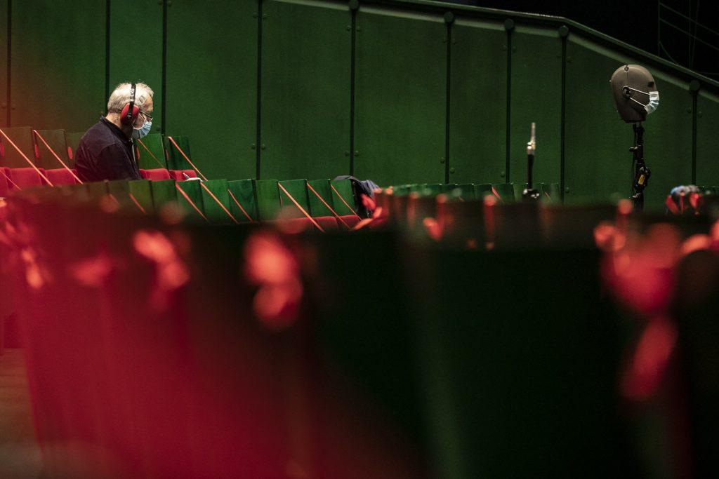 Widownia dużej sceny zabezpieczona czerwonymi wstążkami. Na jednym z krzeseł siedzi mężczyzna w słuchawkach.