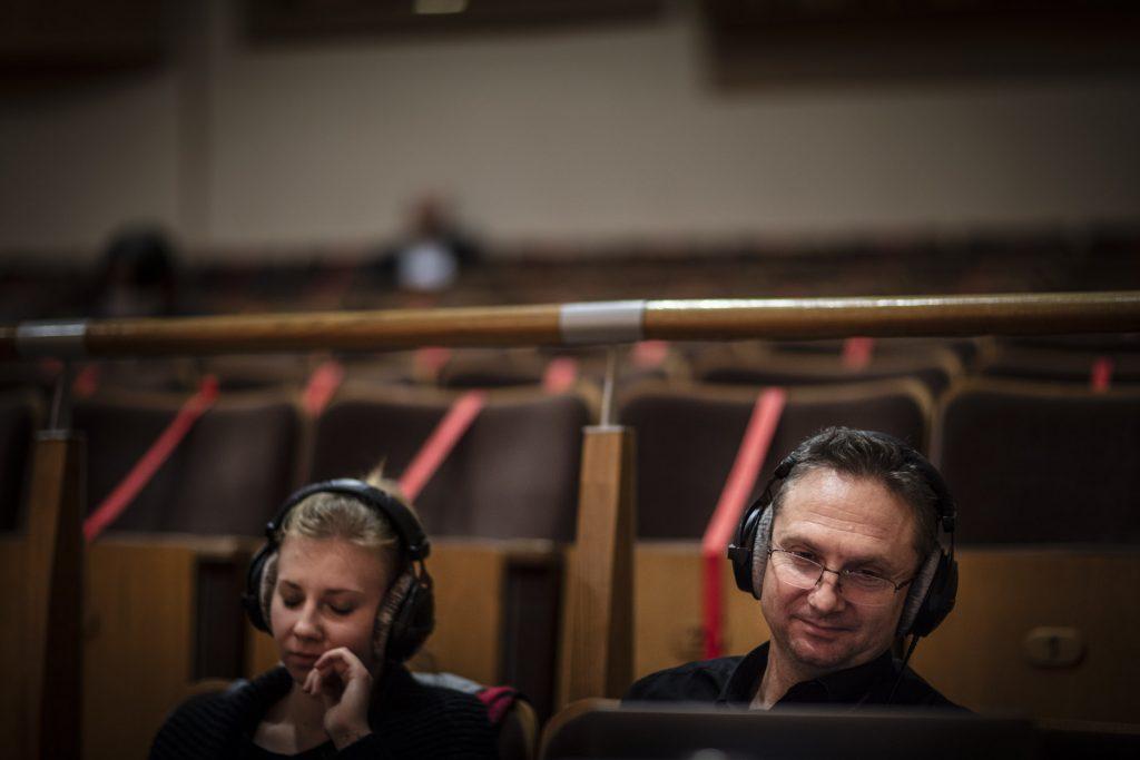 Na widowni, na krzesłach siedzą dwie osoby, kobieta i mężczyzna. Na uszach mają słuchawki.