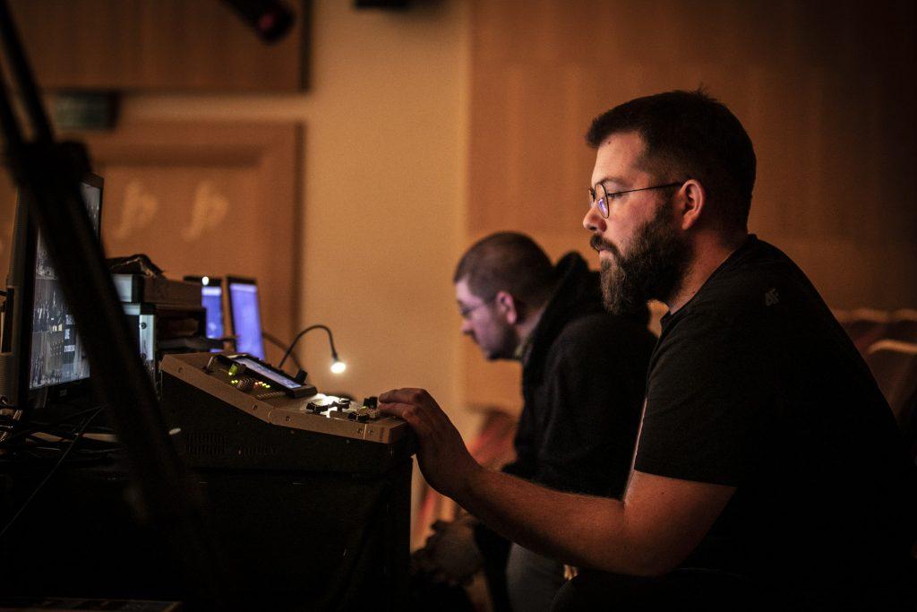 Dwóch mężczyzn siedzi przy konsoletach na widowni.