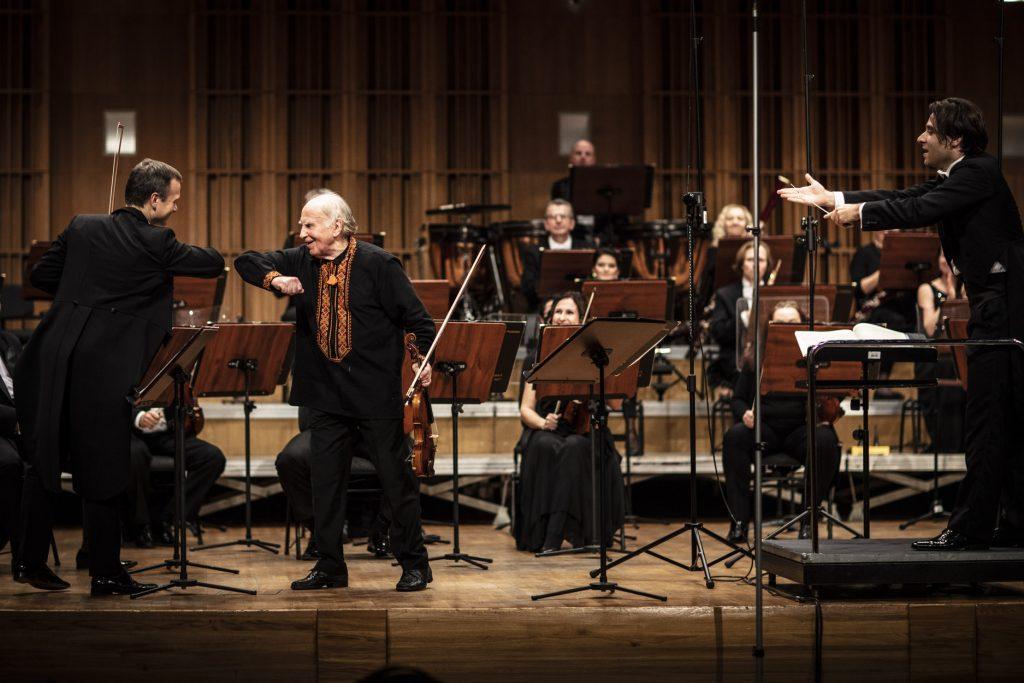 Na scenie z przodu dwóch mężczyzn dotykających się łokciami w geście powitania. Po prawej stronie stoi dyrygent. Za nimi siedzi orkiestra.