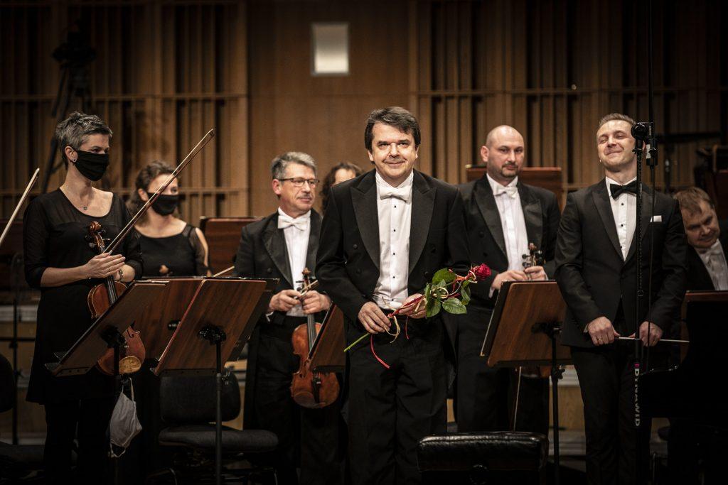 Na środku sceny mężczyzna w czarnym fraku trzyma czerwoną różę. Za nim kilku muzyków z kwintetu smyczkowego orkiestry. Wszyscy stoją.