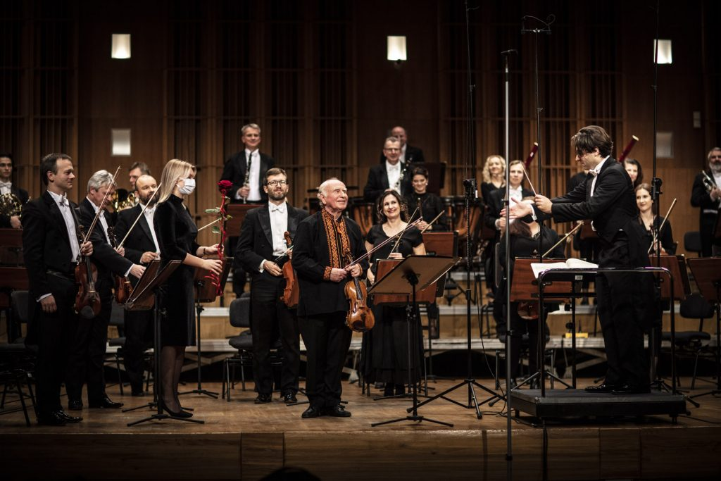 Na scenie stoi Orkiestra Opery i Filharmonii Podlaskiej. Po prawej stronie, na podeście stoi dyrygent, ręką pokazuje na mężczyznę który stoi na środku trzymając skrzypce. Obok stoi kobieta trzymająca różę.