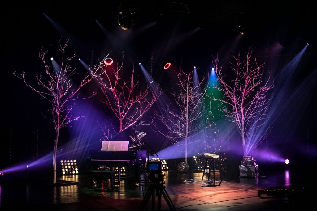 Scena w półmroku, oświetlona niebieskim i różowym światłem. Na scenie fortepian, obok nieco dalej wysokie krzesło. W oddali stoi choinka. Z przodu widać kamerę na statywie.