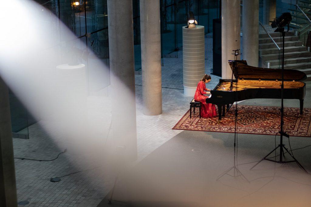 Zdjęcie zrobione z góry. Koncert ma dolnym foyer z cyklu ''Jesień z Chopinem''. Przy fortepianie siedzi kobieta w czerwonej sukni. Obok niej statywy, na jednym z nich reflektor.
