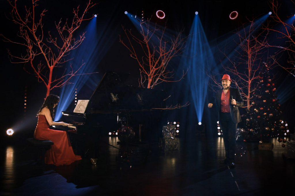 Scena w półmroku, oświetlona niebieskim i czerwonym światłem. Na scenie, przy fortepianie, siedzi kobieta w czerwonej sukni. Po prawej stronie mężczyzna w czerwonej koszuli i kapeluszu. W oddali stoi choinka.