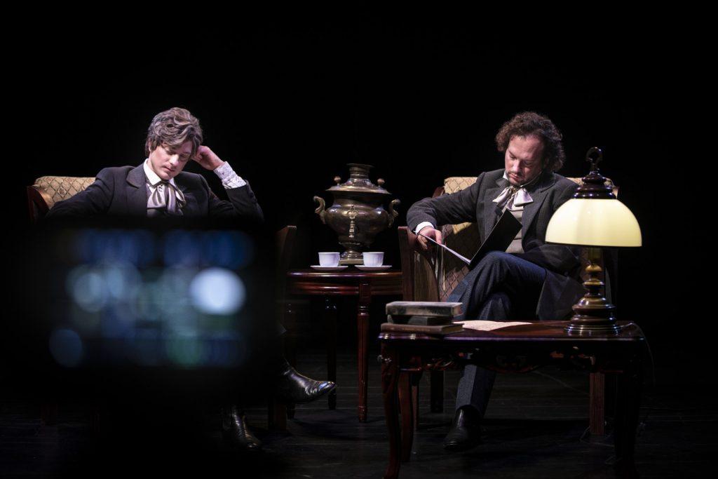 Na stylowych fotelach siedzi dwóch mężczyzn. Ubrani w kostiumy z XIX wieku. Jeden z nich trzyma otwartą teczkę w ciemnej oprawie. Pomiędzy nimi stoi stolik z samowarem i filiżankami. Z przodu drugi stolik z książkami i lampką.