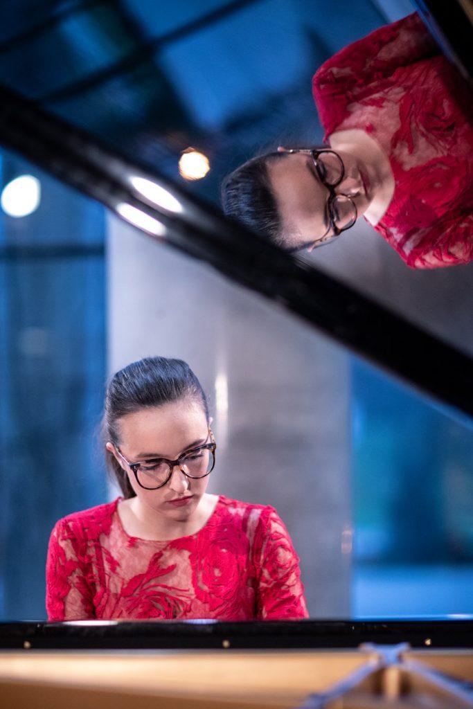 Koncert online transmitowany z dolnego foyer. Kobieta w czerwonej sukni gra na fortepianie.