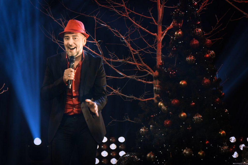 Mężczyzna ubrany w czerwoną koszulę, czerwony kapelusz i czarną marynarkę śpiewa do mikrofonu. Po prawej stronie choinka na której wiszą bombki. Za nią gałęzie drzewa.