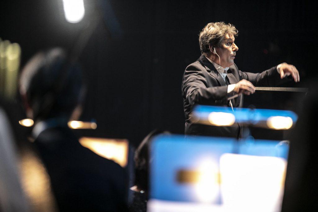 Na zdjęciu z uniesionymi rękoma stoi dyrygent, prof. Mirosław Błaszczyk. Z boku widoczne rozmazane postacie.