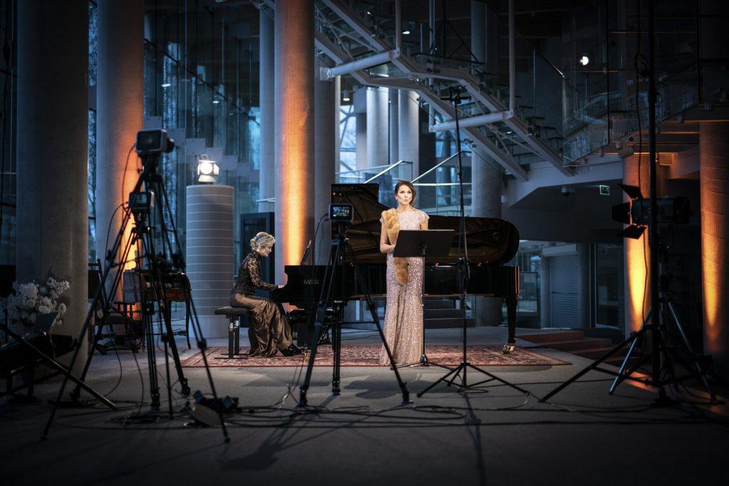 Dolne foyer. Trwa transmisja online koncertu z cyklu ''Jesień z Chopinem''. Na kolorowym dywanie stoi fortepian na którym gra kobieta w eleganckim stroju. Obok stoi kobieta w jasnej, długiej sukni. Przed nimi kilka statywów z lampami, kamerami i aparatami.