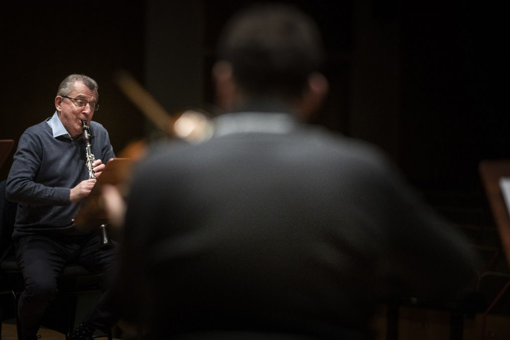 Próba do koncertu. Zdjęcie pokazuje dwóch mężczyzn. Jeden gra na klarnecie, drugi na skrzypcach.